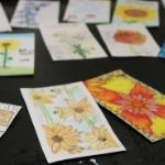 Art students draw and color flowers for seed packets